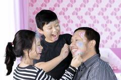 Ojciec i dzieci bawić się z twarz obrazem zdjęcia royalty free