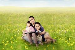 Ojciec i dzieci czytający książkę na łące Fotografia Stock