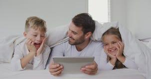 Ojciec i dzieci używa cyfrową pastylkę pod koc na łóżku 4k w domu zbiory