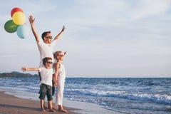 Ojciec i dzieci z balonami bawić się na plaży przy da fotografia stock