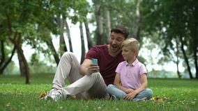 Ojciec i dziecko bierze selfie z smartphone, chwyta szczęśliwego rodzinnego moment zdjęcie wideo