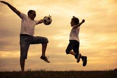 Ojciec i młody mały syn bawić się w polu z piłka nożna półdupkami Obrazy Royalty Free