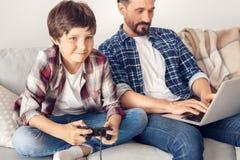 Ojciec i mały syn siedzi na kanapa tacie pracuje na laptopie w domu podczas gdy chłopiec w górę bawić się gemowy radosnego obraz royalty free