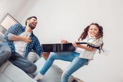 Ojciec i mała córki dziewczyna bawić się gitarę rozochoconą w domu podczas gdy ojca śmiać się obrazy stock