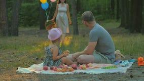 Ojciec i mała dziewczynka relaksuje na koc w parku i czekanie kobiecie z koszem zdjęcie wideo
