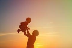 Ojciec i małe syn sylwetki bawić się przy zmierzchem Obrazy Stock
