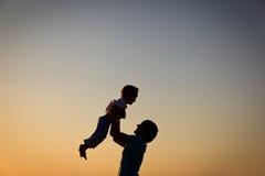 Ojciec i małe syn sylwetki bawić się przy zmierzchem Obraz Royalty Free