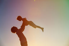 Ojciec i małe syn sylwetki bawić się przy zmierzchem Zdjęcie Royalty Free