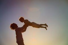 Ojciec i małe syn sylwetki bawić się przy zmierzchem Zdjęcia Stock