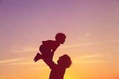 Ojciec i małe syn sylwetki bawić się przy zmierzchu niebem Fotografia Royalty Free