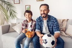 Ojciec i mały syn siedzi na kanapy chłopiec łasowania frytki tacie z balowym dopatrywanie futbolu mistrzostwem w domu obraz royalty free
