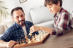 Ojciec i mały syn siedzi przy stołowym bawić się szachowym tatą patrzeje ceerful przy chłopiec mienia rycerzem rozważnym w domu fotografia stock