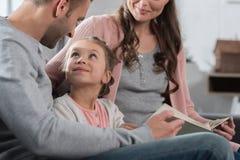 Ojciec i matka nauczania córka czytać zdjęcie stock