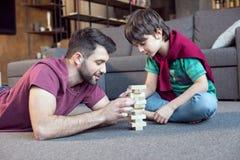 Ojciec i skoncentrowany syn bawić się jenga grę obraz stock