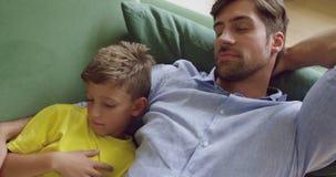 Ojciec i syn śpi wpólnie na kanapie 4k w domu zdjęcie wideo