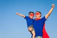 Ojciec i syn bawić się bohatera przy dnia czasem obraz stock