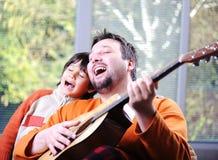 Ojciec i syn bawić się gitarę Obrazy Royalty Free