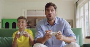Ojciec i syn bawić się gra wideo wpólnie na kanapie 4k w domu zbiory