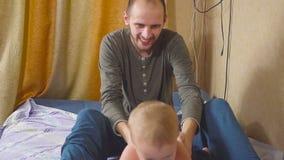 Ojciec i syn bawić się na łóżkowym uściśnięciu i sztuce zbiory wideo