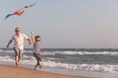 Ojciec i syn bawić się na plaży przy dnia czasem Zdjęcie Royalty Free