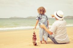 Ojciec i syn bawić się na plaży przy dnia czasem Obraz Royalty Free