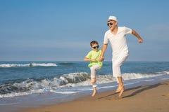 Ojciec i syn bawić się na plaży przy dnia czasem Pojęcie Obrazy Royalty Free