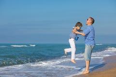 Ojciec i syn bawić się na plaży przy dnia czasem Pojęcie Zdjęcia Stock