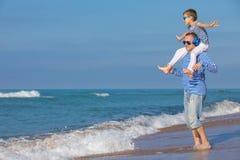 Ojciec i syn bawić się na plaży przy dnia czasem Pojęcie Obraz Stock