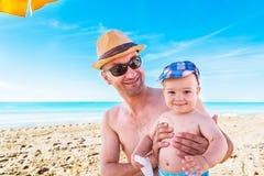 Ojciec i syn bawić się na plaży przy letniego dnia czasem fotografia royalty free