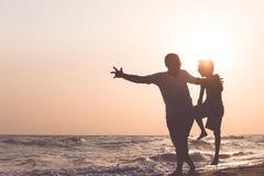 Ojciec i syn bawić się na plaży przy zmierzchu czasem Zdjęcia Stock