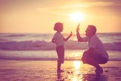 Ojciec i syn bawić się na plaży przy zmierzchu czasem Fotografia Royalty Free