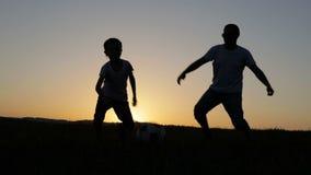 Ojciec i syn bawić się piłkę nożną w parku przy zmierzchu czasem