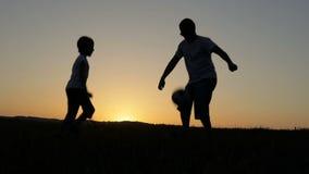 Ojciec i syn bawić się piłkę nożną w parku przy zmierzchu czasem zbiory wideo