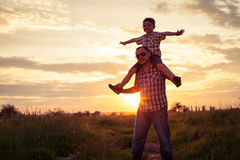 Ojciec i syn bawić się przy parkiem przy zmierzchu czasem fotografia royalty free