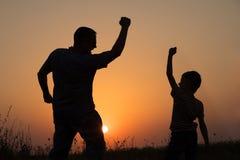 Ojciec i syn bawić się w parku przy zmierzchu czasem Obraz Stock