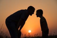 Ojciec i syn bawić się w parku przy zmierzchu czasem Obrazy Stock