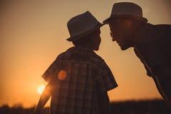 Ojciec i syn bawić się w parku przy zmierzchu czasem obraz royalty free