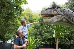 Ojciec i syn bawić się w przygody Dino parku fotografia royalty free