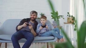Ojciec i syn bawić się wideo gry obsiadanie na kanapie w domu, syn wygrywamy i czujemy excited, śmiający się i zbiory