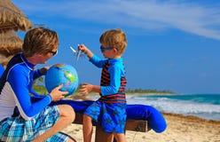 Ojciec i syn bawić się z kulą ziemską na plaży Zdjęcia Stock