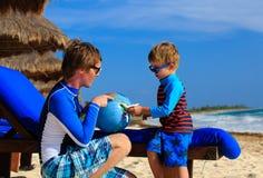 Ojciec i syn bawić się z kulą ziemską na plaży Fotografia Royalty Free