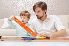 Ojciec i syn bawić się z zabawkarskim budynku zestawem Obraz Stock