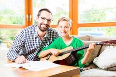 Ojciec i syn bawić się gitarę w domu Obraz Royalty Free