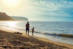 Ojciec i syn cieszymy się wydający czas w rozmowie wpólnie przy piasek plażą z morzem, niebem i górami w tle, na Zdjęcia Royalty Free