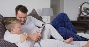 Ojciec i syn czyta opowieść rezerwujemy na łóżku w sypialni 4k zdjęcie wideo