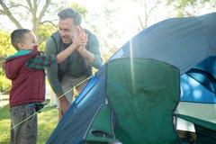 Ojciec i syn daje wysocy pięć po utworzenia namiotowi Zdjęcie Stock