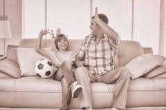Ojciec i syn daje wysokości podczas gdy oglądający mecz piłkarskiego Obrazy Royalty Free