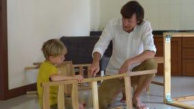 Ojciec i syn gromadzić drewnianego meble od małych części Chłopiec pomaga jego ojca gromadzić krzesła zdjęcie wideo