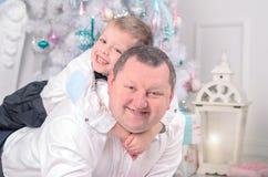 Ojciec i syn kłama blisko choinki, ono uśmiecha się, szczęśliwy zdjęcia stock