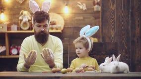 Ojciec i syn malujemy jajka Szczęśliwa rodzina przygotowywa dla wielkanocy Śliczna małe dziecko chłopiec jest ubranym królików uc zbiory wideo